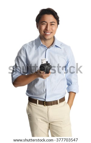 An attractive man in his 20s, standing against a white background wearing a blue shirt with beige pants, holding a black piggy bank with a dollar bill in it. Smiling.