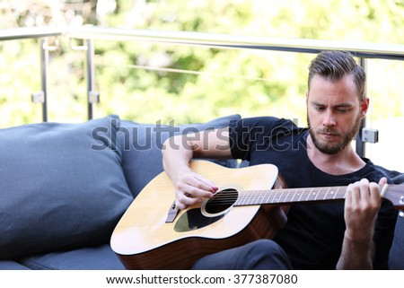 An attractive man in his 20s wearing a black t shirt, sitting down outside on a summer day playing his acoustic guitar. Looking away from camera. - stock photo