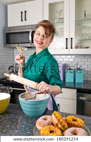An attractive middle-aged woman in a kitchen wearing a vintage dress, holding a martini in one hand and a rolling pin in the other with cooking items around her, smiling - stock photo