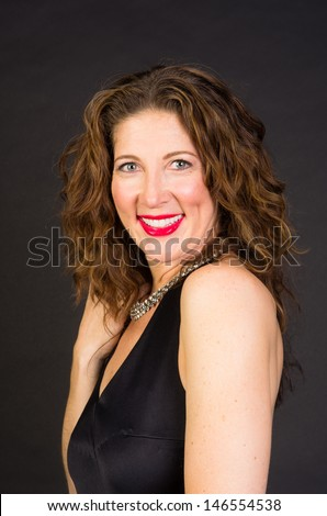 An attractive middle aged woman in black dress shot on black background