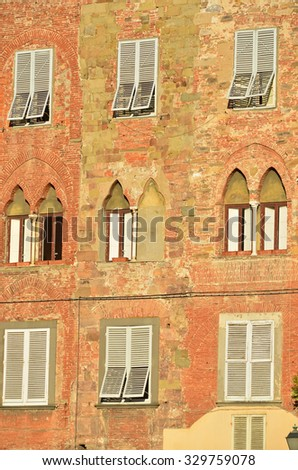 An attractive mixture of stone and brick and gothic arches in the wall of a large Italian town house, Lucca, Italy - stock photo