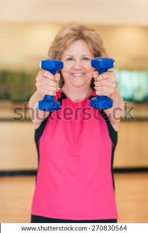 An attractive older woman smiles as she holds hand weights straight out towards the camera in an exercise studio.  The plastic-coated blue dumbbells are in sharp focus, and the woman is in background. - stock photo