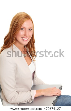 An attractive red haired businesswoman wearing a beige jacket and jeans, sitting down holding a laptop computer. White background.