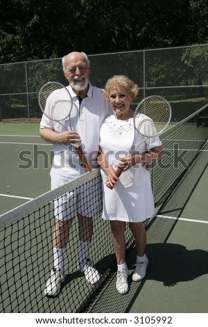 An attractive senior couple on the tennis courts.  Full view vertical. - stock photo