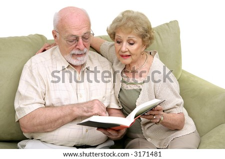 An attractive senior couple spending time reading together. Isolated on white. - stock photo