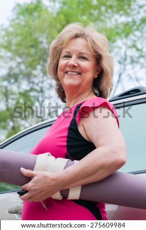 An attractive senior woman stands in front of an SUV.  She is holding a purple yoga mat wrapped with a yoga strap under one arm.  She wears bright pink active-wear and holds car keys in her hand.   - stock photo