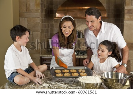 An attractive smiling family of mother, father, and two children baking and eating fresh chocolate chip cookies in a kitchen at home - stock photo