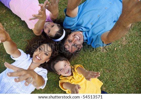 An attractive smiling family of mother, father, and two children laying down on grass outside having fun with arms and hands outstrectched to the camera - stock photo