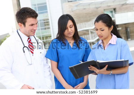 An attractive successful man and woman medical team outside hospital - stock photo