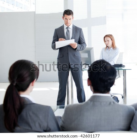 An attractive team leader talking to his colleagues in an office - stock photo