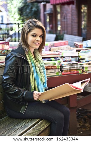 An attractive teen girl looking up from the book she's holding at an outdoor book sale.