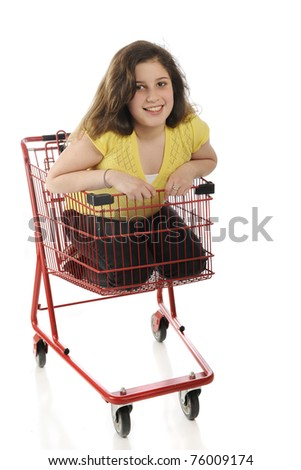 An attractive tween girl riding inside a bright red shopping cart.  Isolated on white.