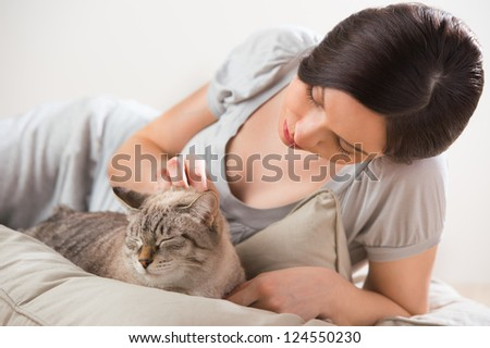 An attractive woman and her cat relaxing on pillows on floor at home