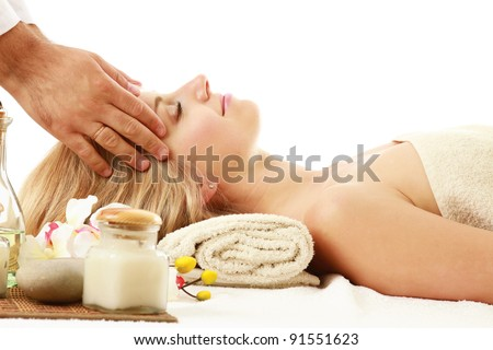 An attractive woman getting spa treatment isolated on white background - stock photo