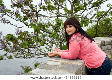 An attractive woman leans up against the wall along the historic Newport coast along the cliff walk path.