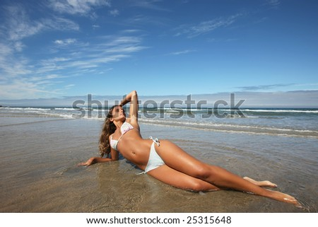 An attractive woman lying on the beach