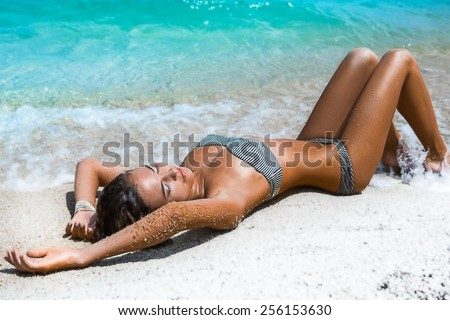 An attractive woman lying on the beach - stock photo