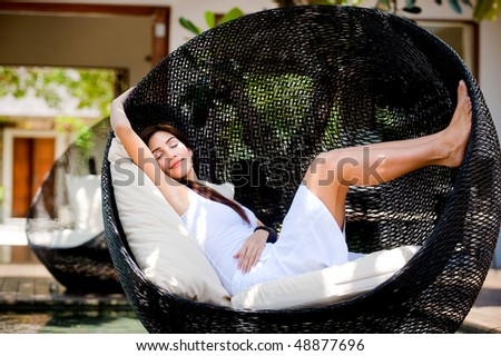 An attractive woman relaxing on a lounge chair outdoors - stock photo