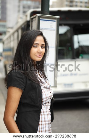 An attractive woman standing at a bus stop looking at viewer.