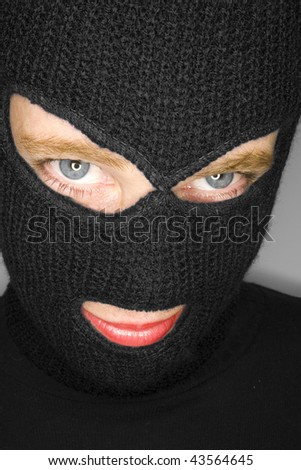 an attractive woman wearing a balaclava. - stock photo