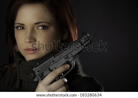 An attractive woman with a gun - stock photo