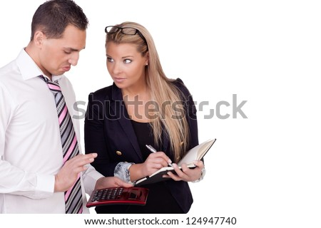 An attractive young businesman and businesswoman standing close together as he makes makes a calculation on a handheld calculator isolated on white with copyspace - stock photo