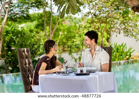 An attractive young couple having a meal outdoors together