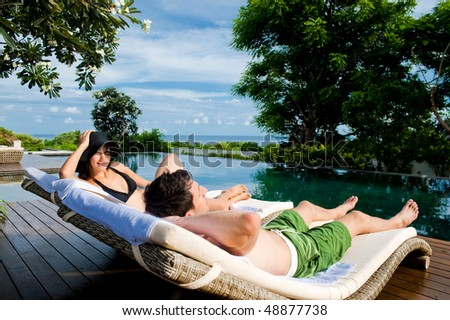 An attractive young couple in swimwear relaxing by the pool outdoors - stock photo