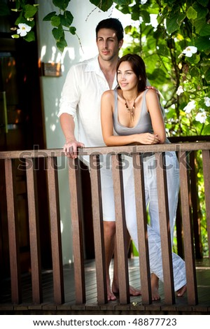 An attractive young couple relaxing outdoors together - stock photo