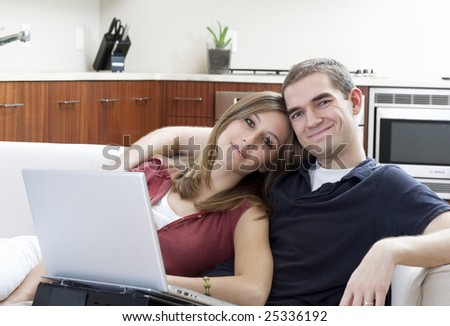 An attractive young couple use a laptop together in a modern home.