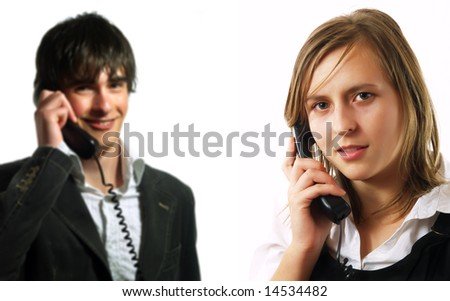 An attractive young customer service representative lady and a young call center operator guy are smiling and they are talking to their clients using wire phones. They are wearing elegant shirts.