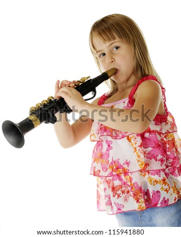 An attractive young elementary girl playing a plastic clarinet.  On a white background.