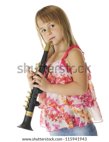 An attractive young elementary girl standing at the ready with her plastic saxophone.  On a white background.