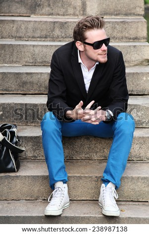 An attractive young man sitting down outside wearing a black jacket with sunglasses and blue jeans. Summer day with sun shining. - stock photo