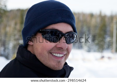 An attractive young man smiling while outside in the winter wearing sunglasses, a hat and coat. - stock photo