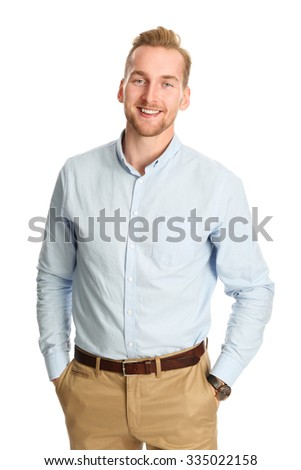 An attractive young man wearing a blue shirt with khaki pants, standing smiling towards camera against a white background.