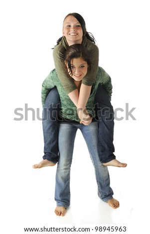 An attractive young teen giving her friend a piggyback ride.  Isolated on white.
