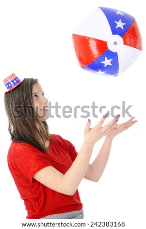 An attractive young teen wearing a tiny Uncle Sam hat.  She's playing catch with an inflated star-studded red, white and blue ball.  On a white background. - stock photo