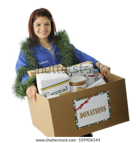 An attractive young volunteer holding a large box of food donated for the holidays.  On a white background. - stock photo