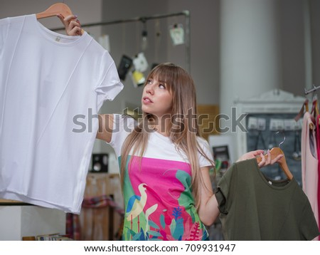 An attractive young woman buying T-shirts in a shop on a light gray background. Shopping, shop, goods, clothes, dress, purchases concept.
