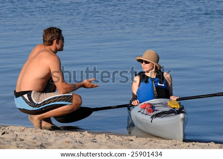 An attractive young woman discusses sea kayaking with a man on a beach. Mission Bay, San Diego, California