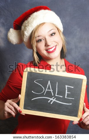 An attractive young woman displays a sale sign for the Christmas season.