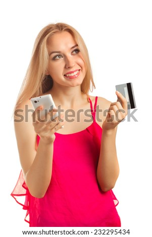 An attractive young woman doing some on-line shopping while holding a credit card isolated on white - stock photo