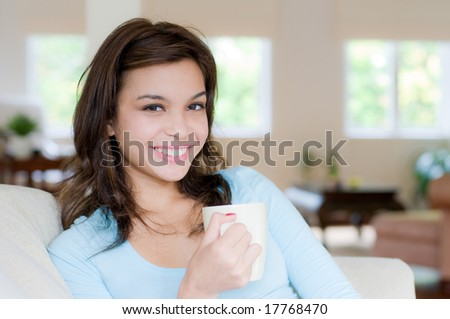 An attractive young woman drinking coffee at home - stock photo