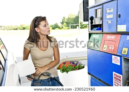 An attractive young woman fills up her SUV/Expensive Gasoline Purchase/ Colors Have Been Changed/ No Identifying Marks - stock photo