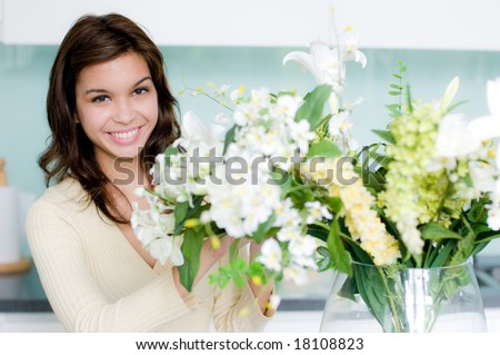 An attractive young woman flower arranging at home - stock photo