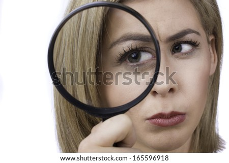 An attractive young woman gazes through a large magnifying glass.