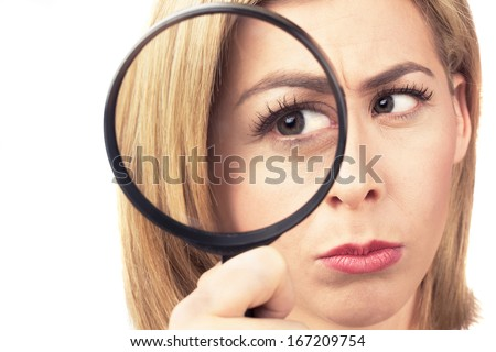 An attractive young woman gazes with one eye through a large magnifying glass. - stock photo
