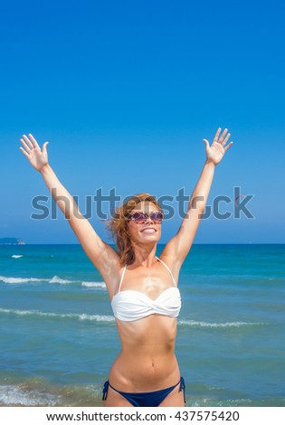 An attractive young woman having fun at the beach - stock photo