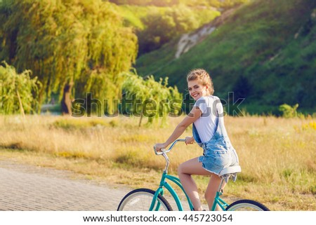 An attractive young woman having fun riding her bicycle - stock photo